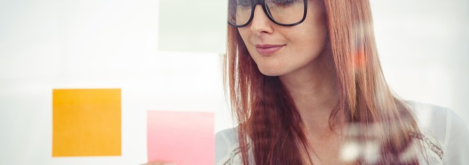 Attractive hipster woman looking at sticky notes